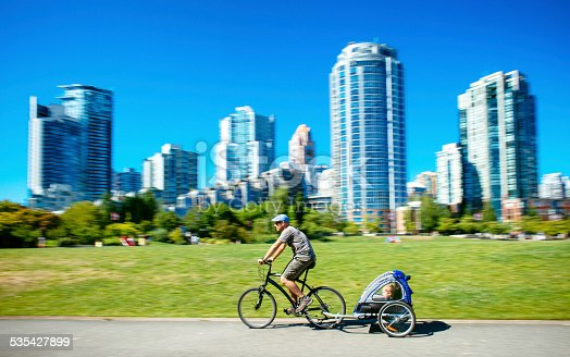 Father carries son in bicycle trailer in Vancouver. Canada.