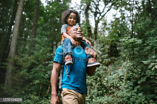 A young mixed race family spends time together outside in Washington state, enjoying the beauty of the woods in the PNW.  The dad holds his boy on his shoulders.