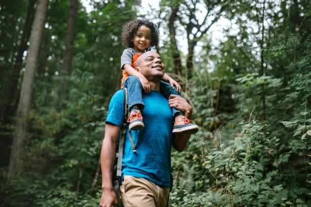 padre lleva a su hijo en caminata a través de sendero forestal en el noroeste del pacífico - excursionismo fotografías e imágenes de stock