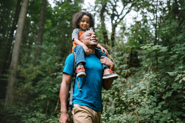 Father Carries Son On Hike Through Forest Trail in Pacific Northwest