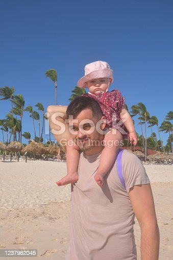 Father Carrying 15 Month Old Toddler on Shoulders at a Sunny Tropical Beach