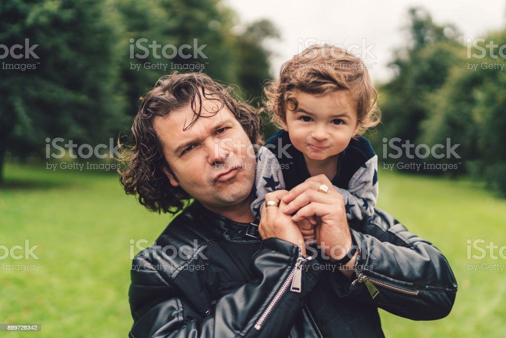 Father carrying a baby on shoulders stock photo