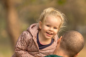 Father carrying adorable smiling daughter with the blonde hair outside in the park.