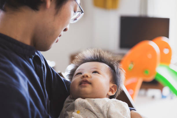 Father carrying baby boy at home Japanese father taking care of his baby boy. stay at home father stock pictures, royalty-free photos & images