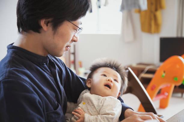 父の家で男の子の赤ちゃんを運ぶ ストックフォト