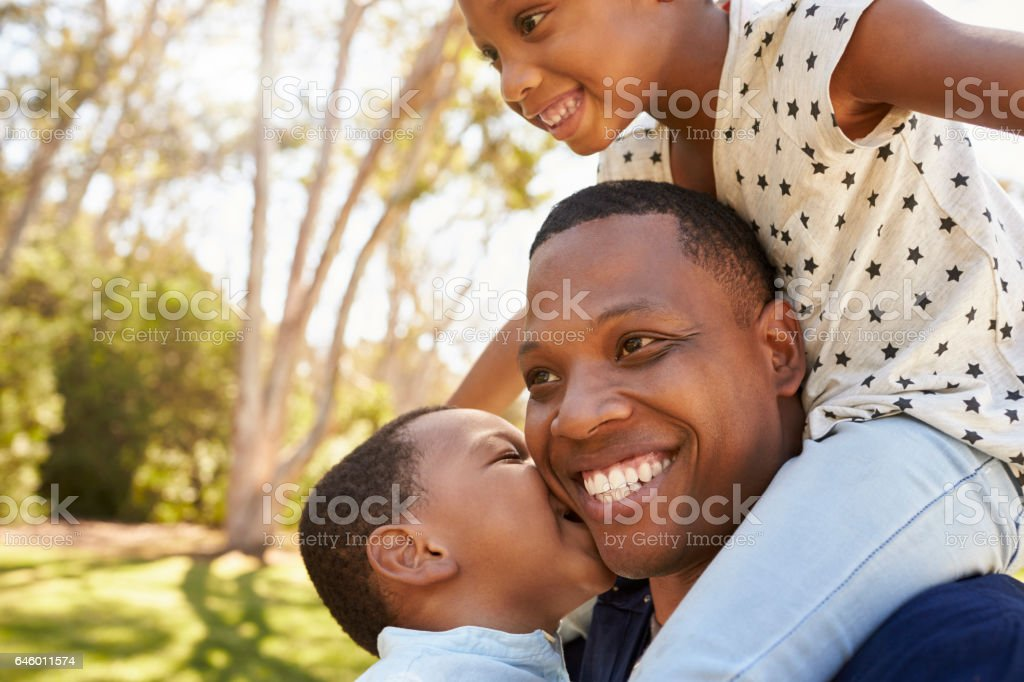 Father Carrying Children On Shoulders As They Walk In Park stock photo