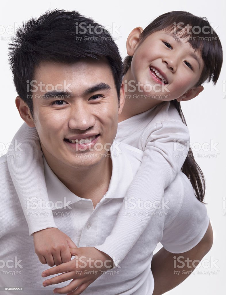 Father carrying daughter on back, studio shot royalty-free stock photo
