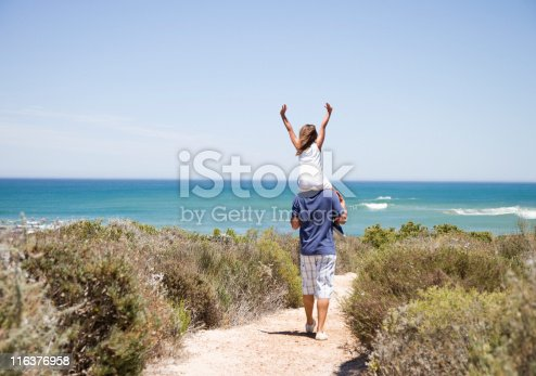 istock Father carrying daughter on shoulders on beach path 116376958