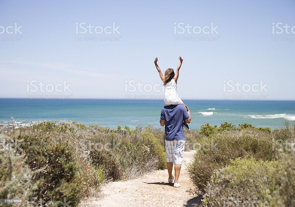 Father carrying daughter on shoulders on beach path stock photo