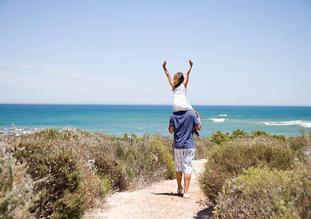 père portant sa petite fille sur les épaules sur le chemin menant à la plage - fille dos photos et images de collection