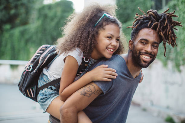 Father carrying daughter on shoulders stock photo