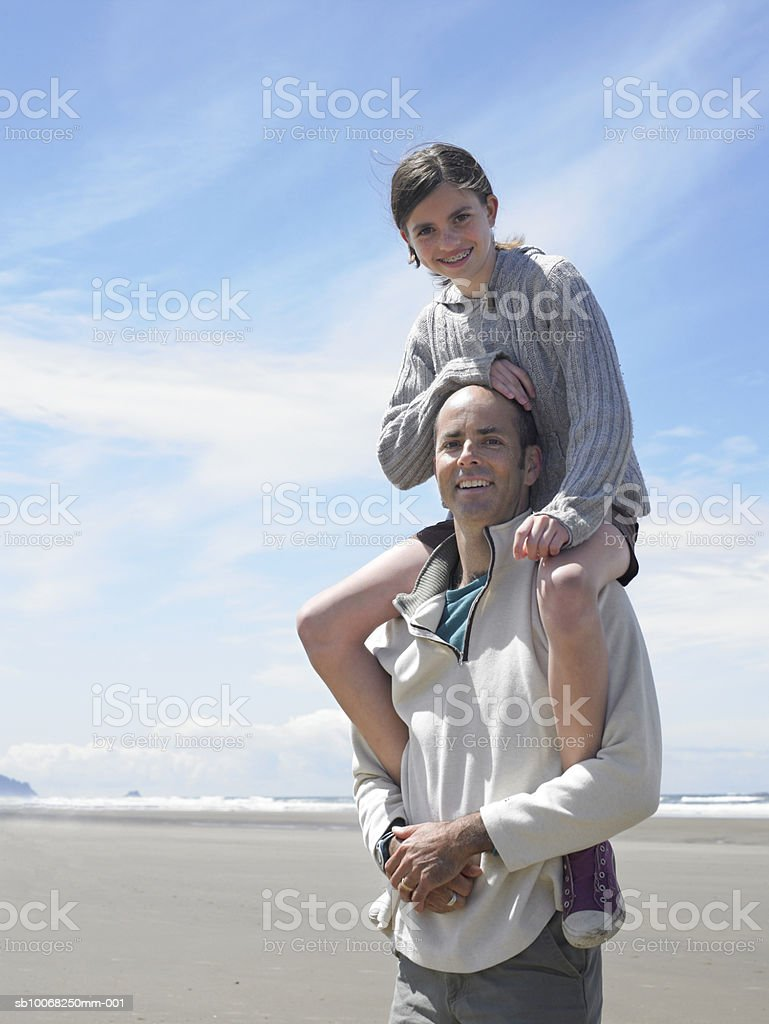 Father carrying daughter (12-13) on shoulders, smiling, portrait royalty-free stock photo