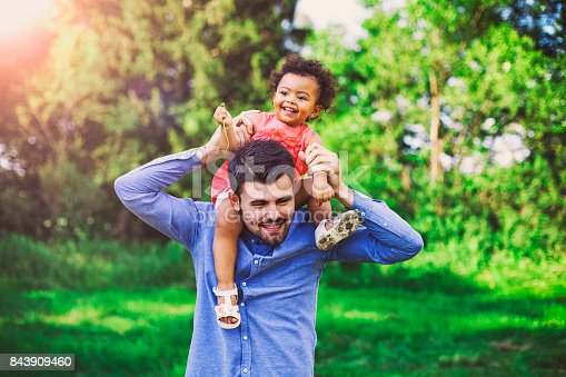istock Father carrying daughter piggyback in the park 843909460