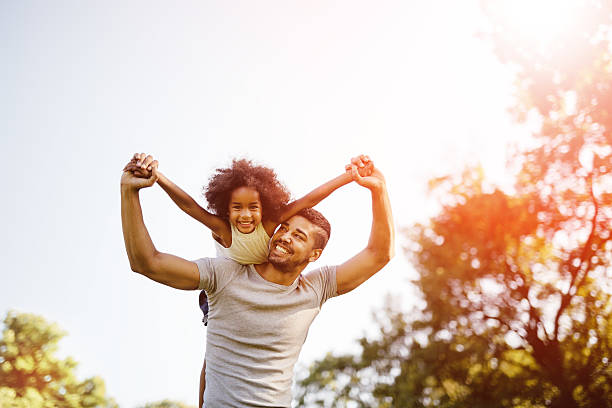 father carrying daughter piggyback - father and daughter stock photos and pictures