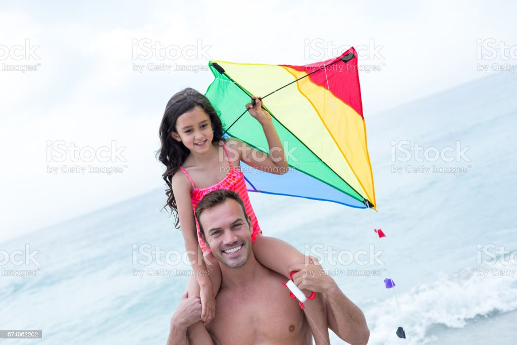 Father carrying daughter with kite at beach royalty-free stock photo