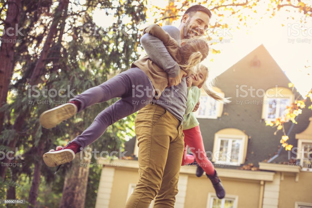 Father carrying daughters around neck.  Side view. stock photo