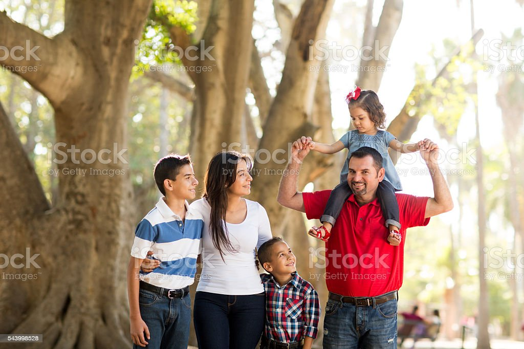 Father carrying girl on shoulders with family stock photo