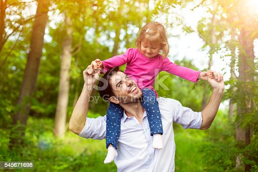 istock Father carrying her daughter on shoulders in nature. 545671698