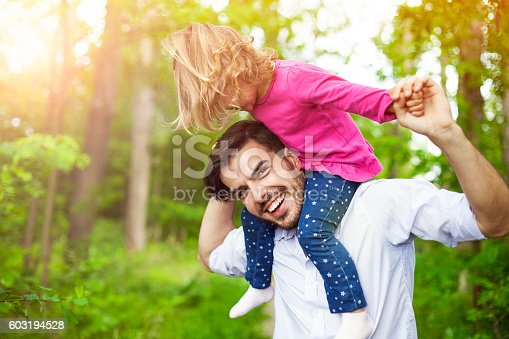 istock Father carrying her daughter on shoulders in nature. 603194528