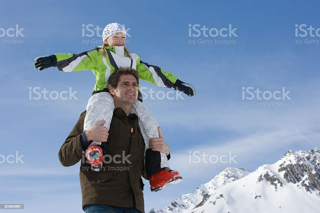 A father carrying his daughter on his shoulders royalty free stockfoto