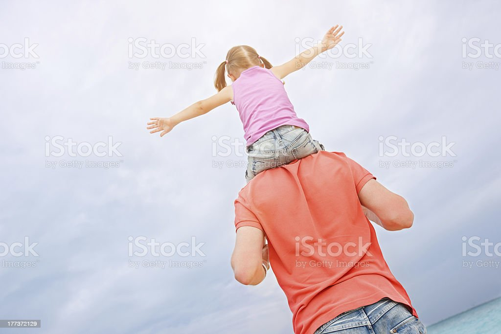 Father carrying his daughter on shoulders stock photo