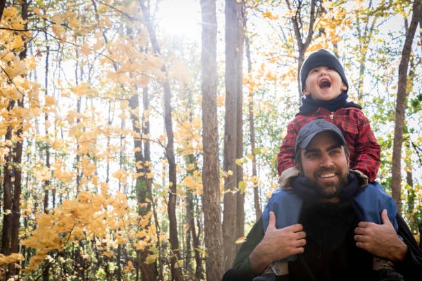 Father Carrying his Son on Shoulders in the Forest in Autumn stock photo