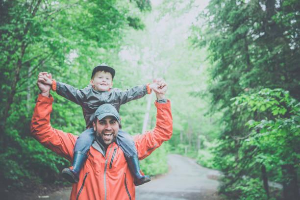 Vater trägt seinen Sohn im Sommer auf Schultern im Wald – Foto