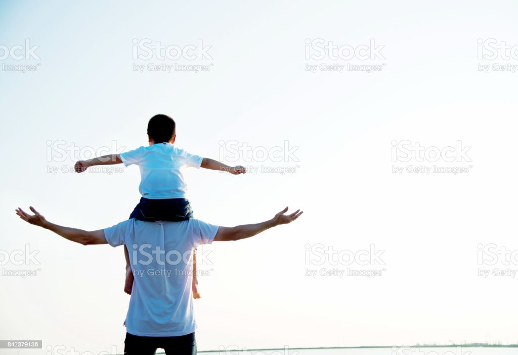 Father carrying his son on shoulders stock photo