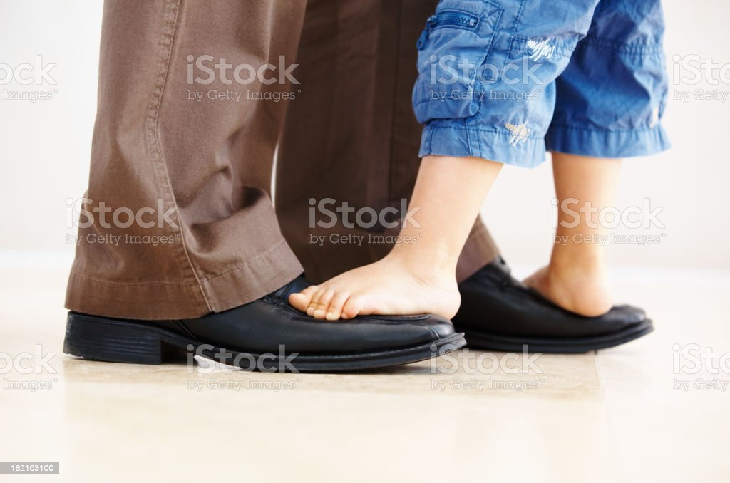 Father carrying son on his feet royalty-free stock photo