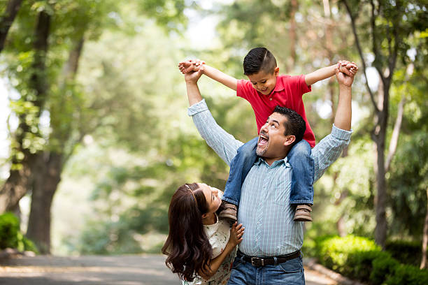 Father carrying son on shoulders and smiling at each other stock photo