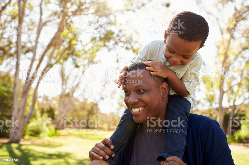 Father Carrying Son On Shoulders As They Walk In Park stock photo