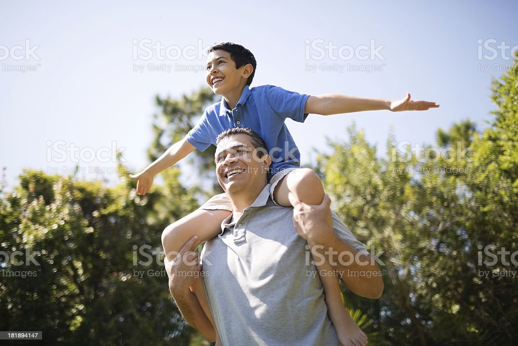 Father Carrying Son On Shoulders In Park royalty-free stock photo