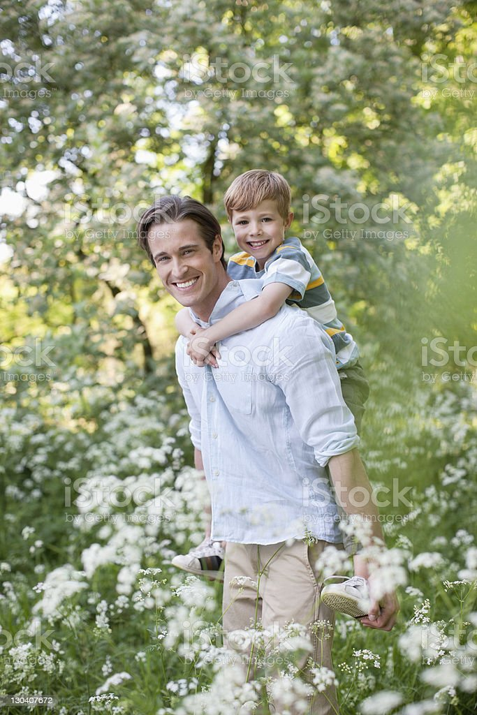 Father carrying son piggyback in field of flowers royalty-free stock photo