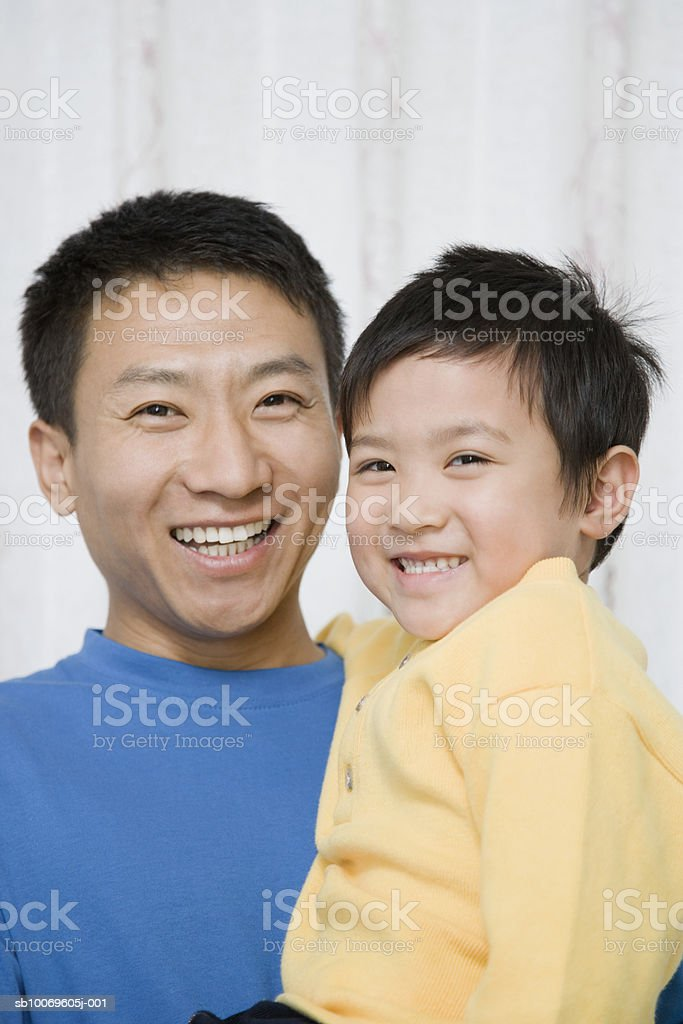Father carrying son (4-5), smiling, portrait foto royalty-free