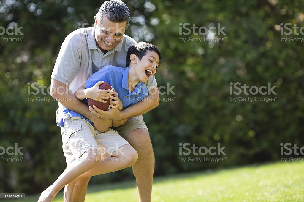 Father Carrying Son While Playing American Football stock photo