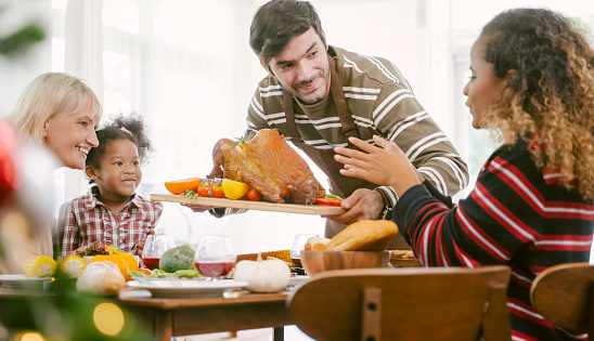 istock father carrying turkey served for family on thanksgiving dinner .Thanksgiving Celebration tradition concept 1177634973