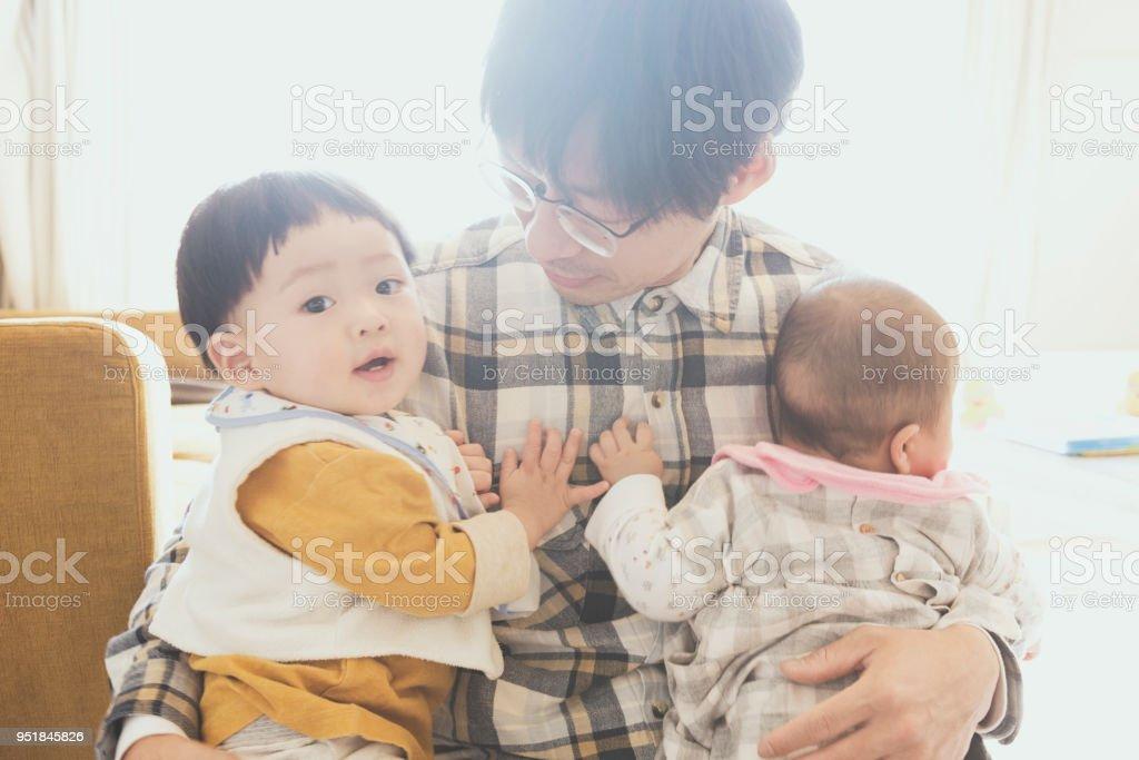 父は自宅に運ぶ 2 つの赤ちゃん ストックフォト