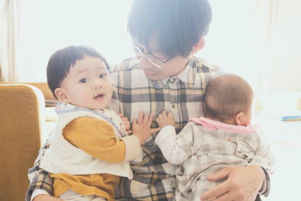 padre con dos bebés en casa - padre que se queda en casa fotografías e imágenes de stock