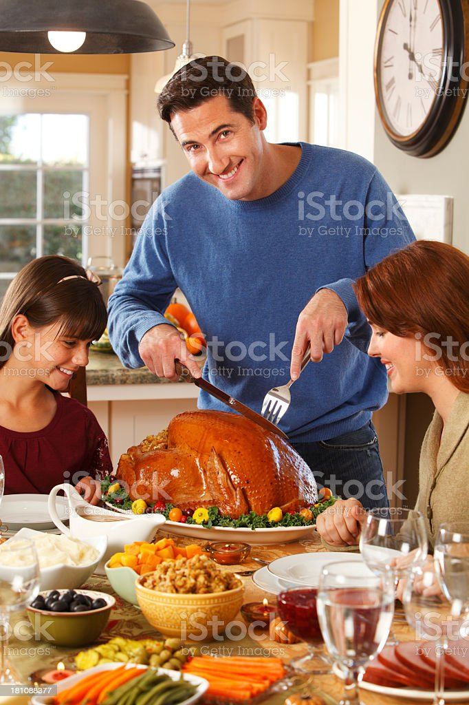 Father Carving Turkey for Thanksgiving Dinner royalty-free stock photo