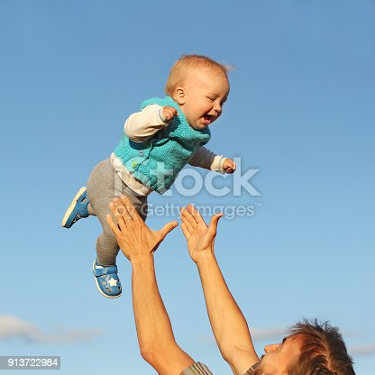 istock father catches his son, flying in the sky, having fun 913722984
