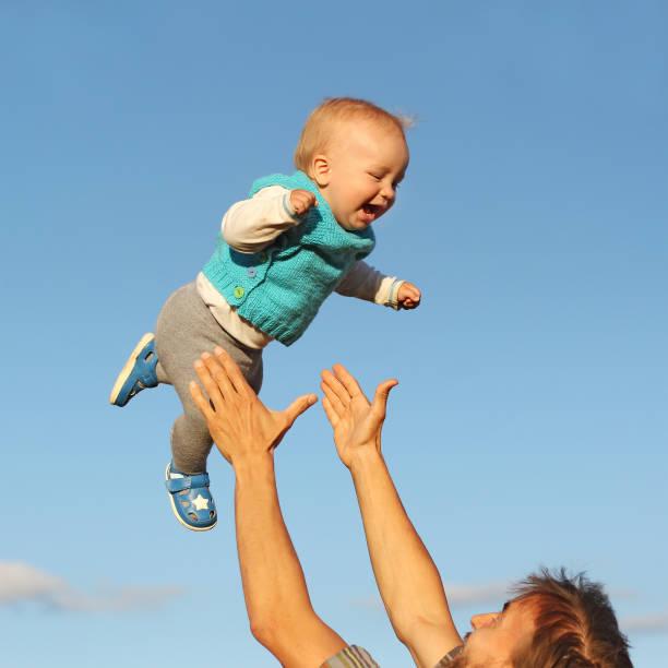 pai pega seu filho, voando no céu, se divertindo - foto de acervo