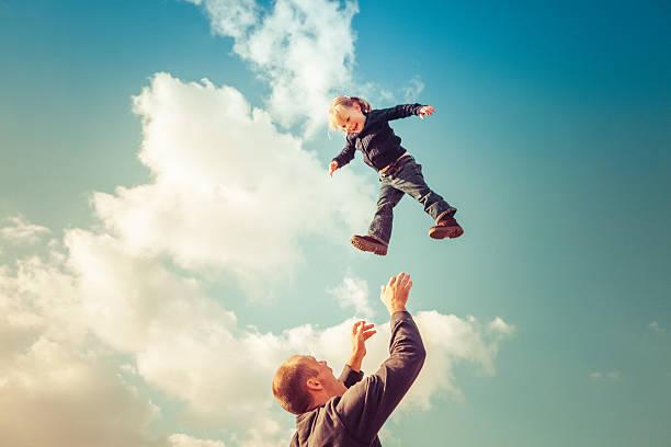 Père regarder fille tomber du ciel nuageux - Photo