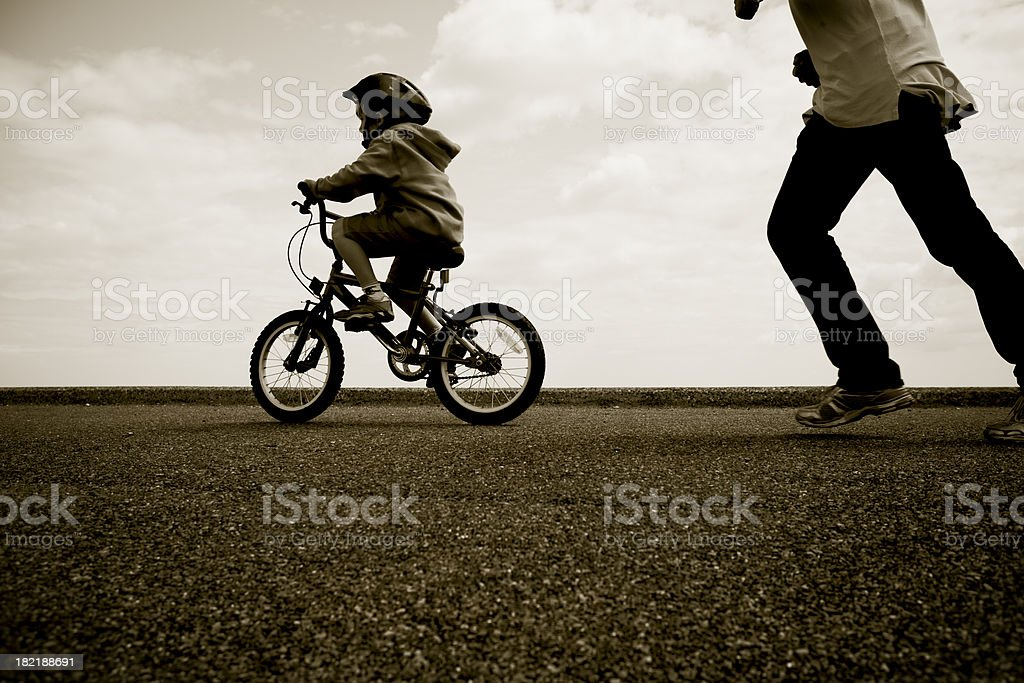 Father chasing young cyclist learning to ride stock photo