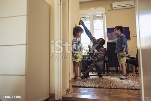 Father checking height of his children