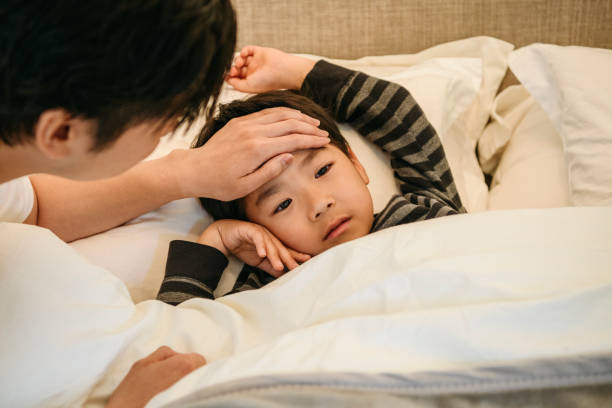 Father checking son's temperature with hand on forehead stock photo