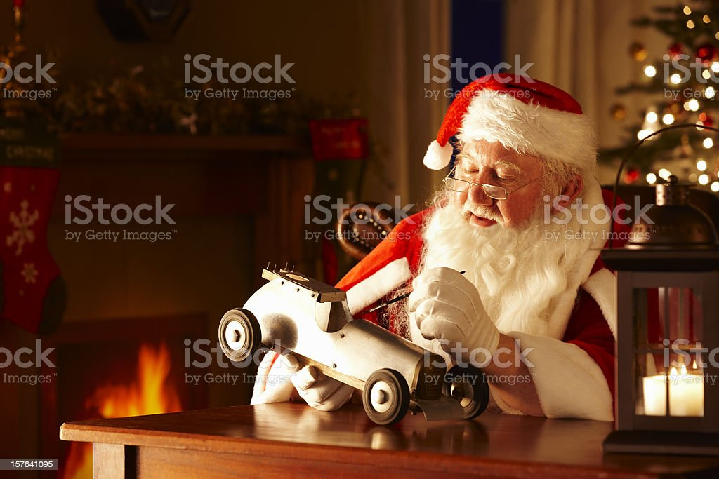 Father Christams painting a toy car in his workshop royalty-free stock photo