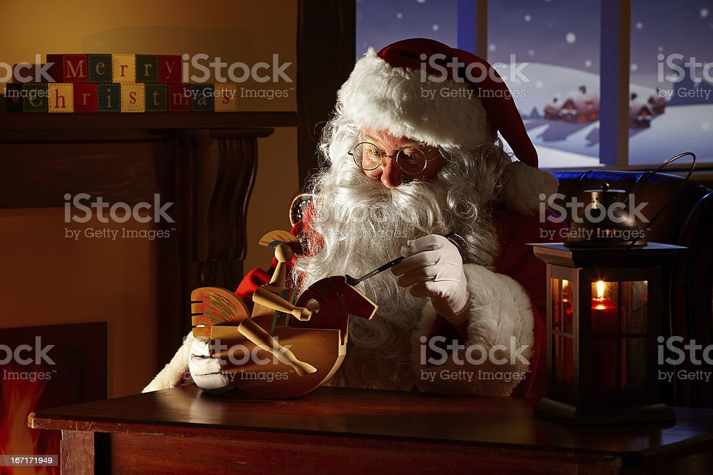 Father Christams painting a toy in his workshop royalty-free stock photo