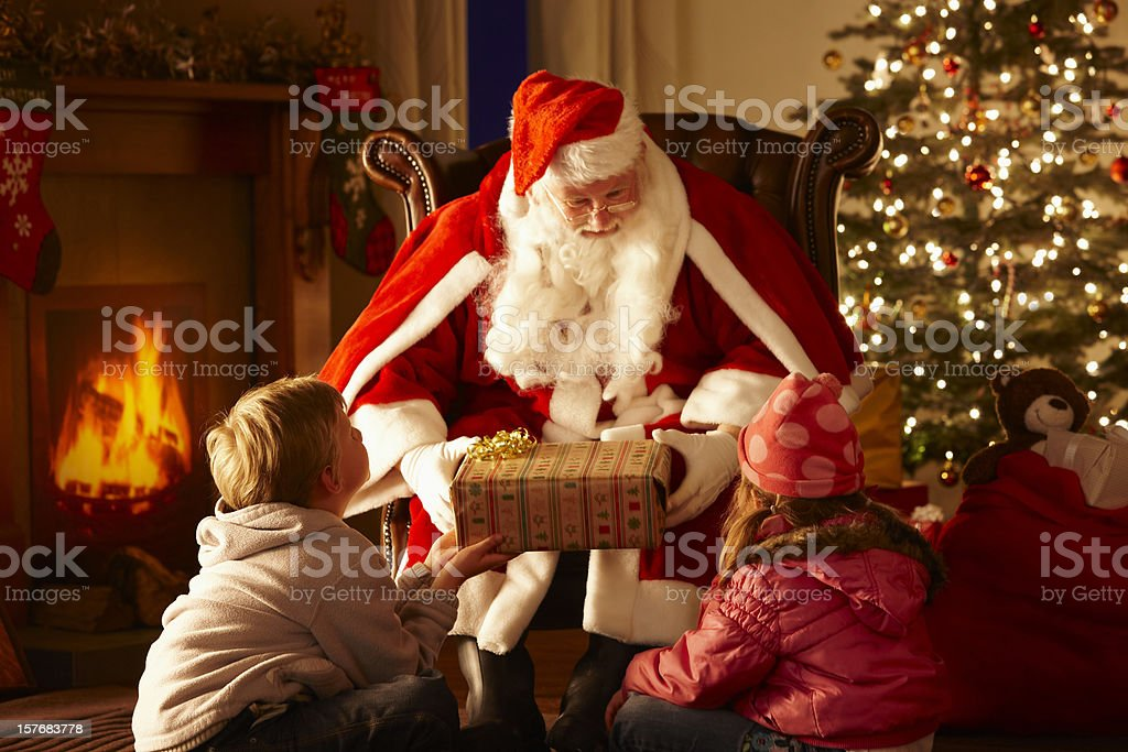Father Christmas giving gift to children in grotto stock photo