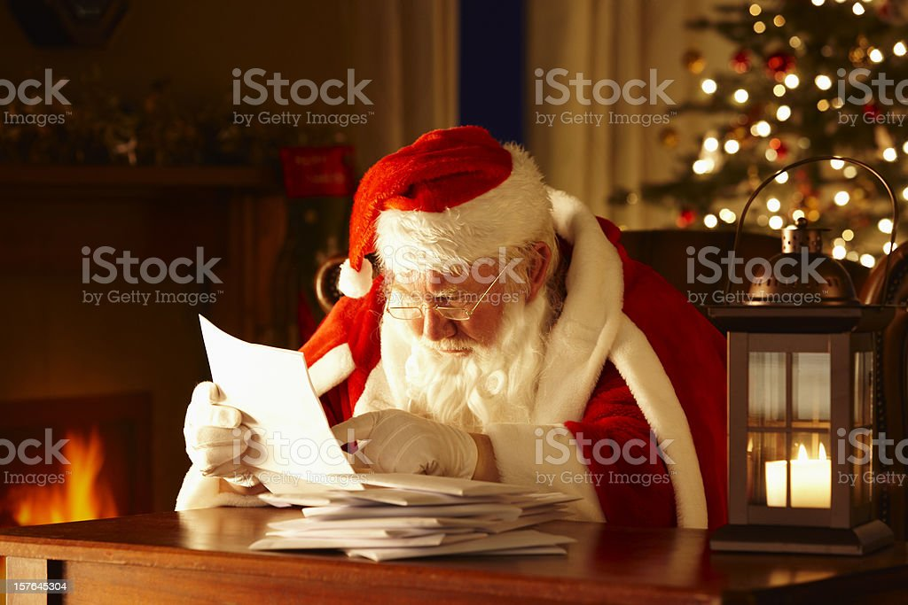 Father Christmas Sat On Chair Looking at Letters stock photo