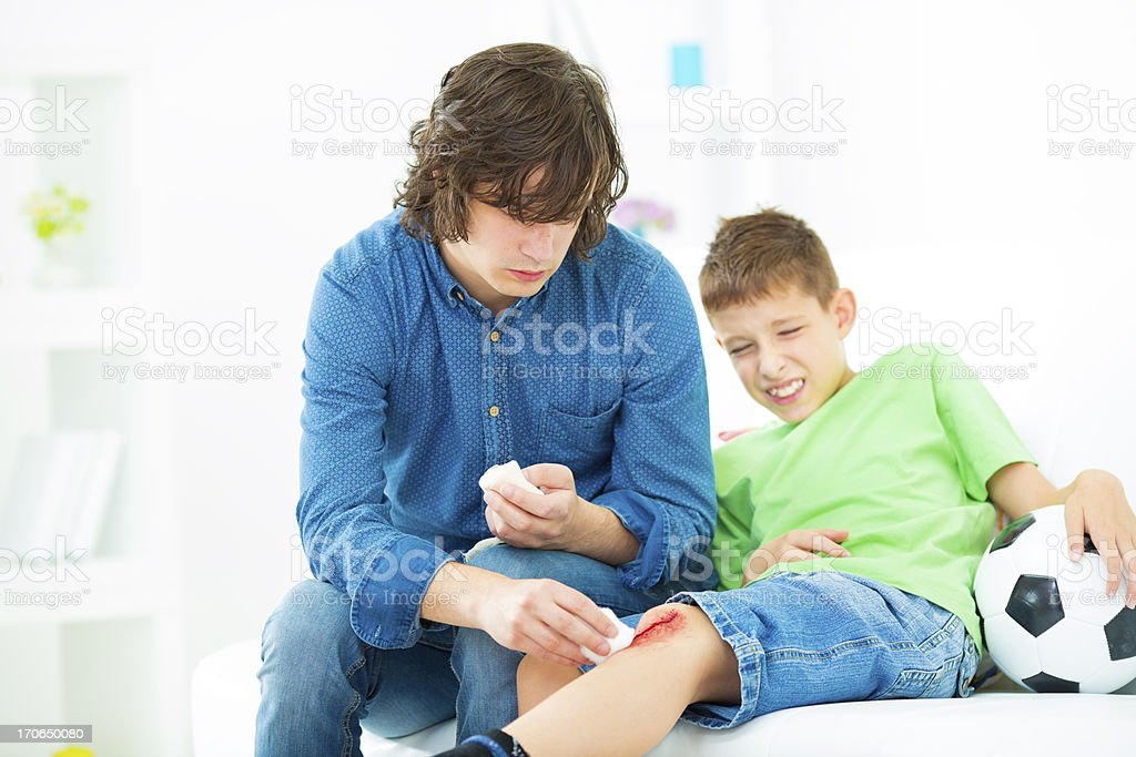 Father Cleaning sons scraped knee. royalty-free stock photo